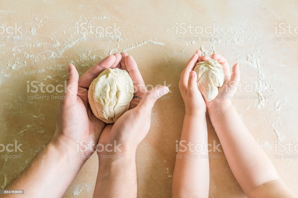Children's and dad's hands makes raw dough stock photo