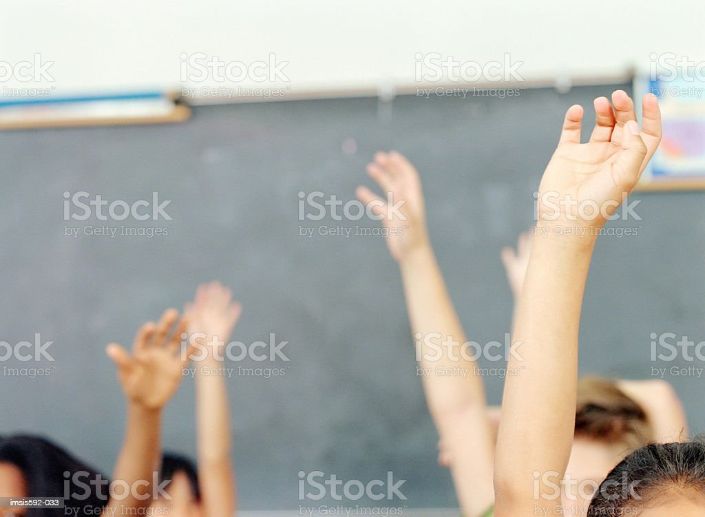 Children's arms raised in classroom royalty free stockfoto