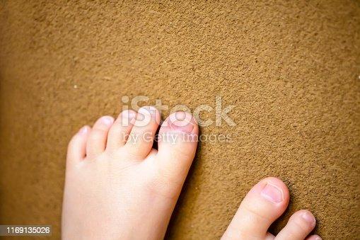 istock Children's bare feet. Child's bare feet on brown background. 1169135026