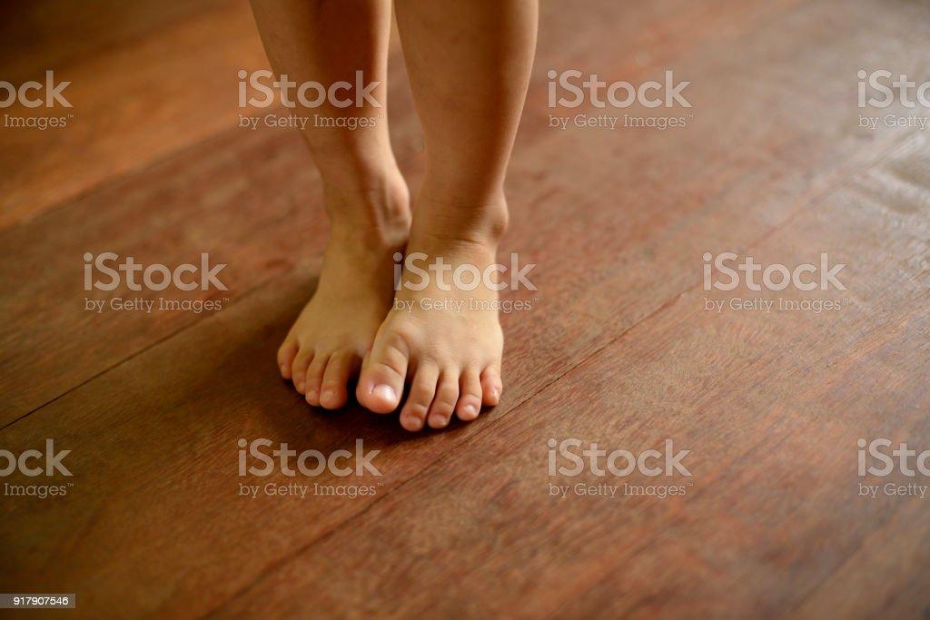 Children's bare feet on wooden floor. – zdjęcie