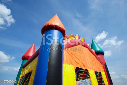 Stock photo of the top half of a children's inflatable bouncy castle with a blue sky and clouds.