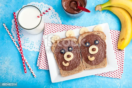 istock Children's breakfast with toasts and milk. Funny bear face sandwiches with chocolate paste, banana, nuts, and berries 692462314