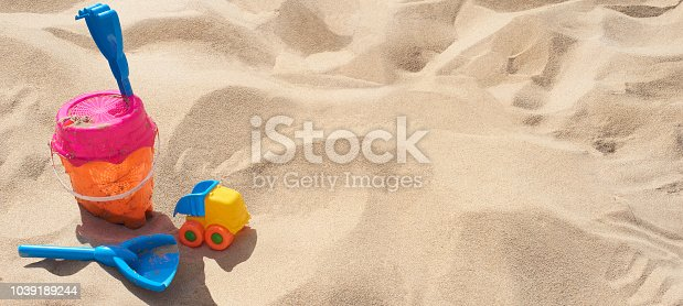 A child's bucket and spade on the beach whilst on holiday