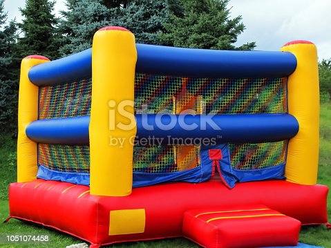 Colorful square children's bounce house with reds, blues, and yellows