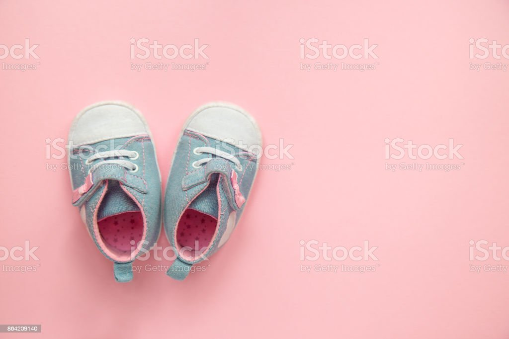 Children's denim sports shoes for girls, stands on a pink backgr royalty-free stock photo