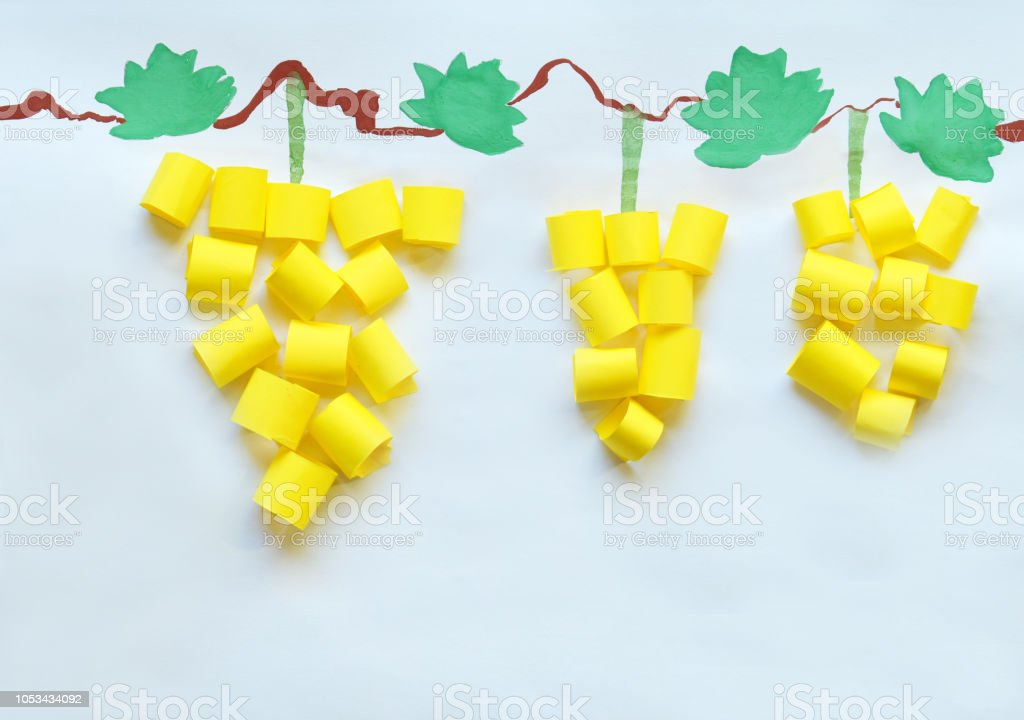 Children's drawing and applique. Yellow grapes made of paper and water-colored leaves. Children DIY stock photo