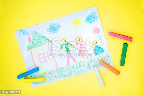 istock Children's drawing of a family with colored crayons on a yellow background 1146968099