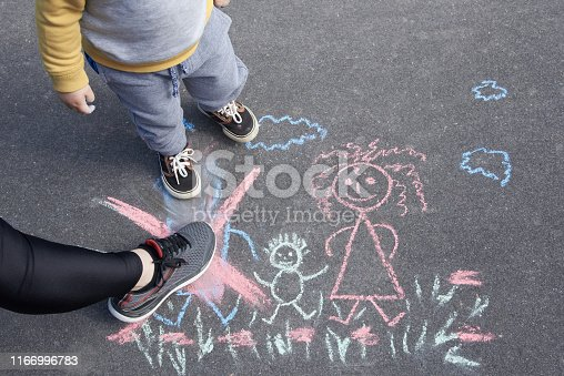 1166996797 istock photo Children's drawing with chalk on the asphalt, family with no dad. Son and mother crossed out father. Family divorce. 1166996783