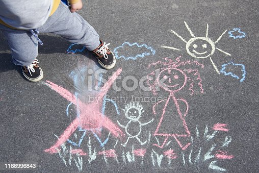 1166996797 istock photo Children's drawing with chalk on the asphalt, family with no dad. Son crossed out father. Family divorce topic. 1166996843