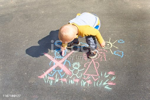 1166996797 istock photo Children's drawing with chalk on the asphalt, family with no dad. Son crossed out father. Family divorce topic. 1167189127