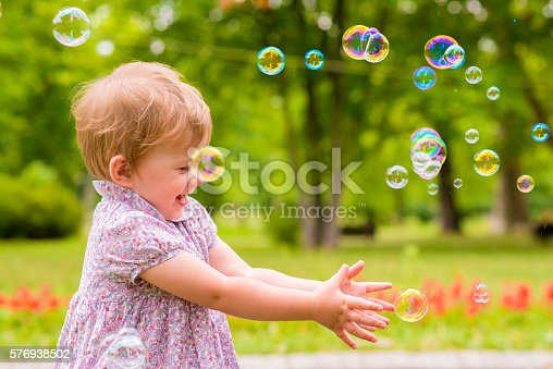 istock children's entertainment, Child playing with soap bubbles outsid 576938502
