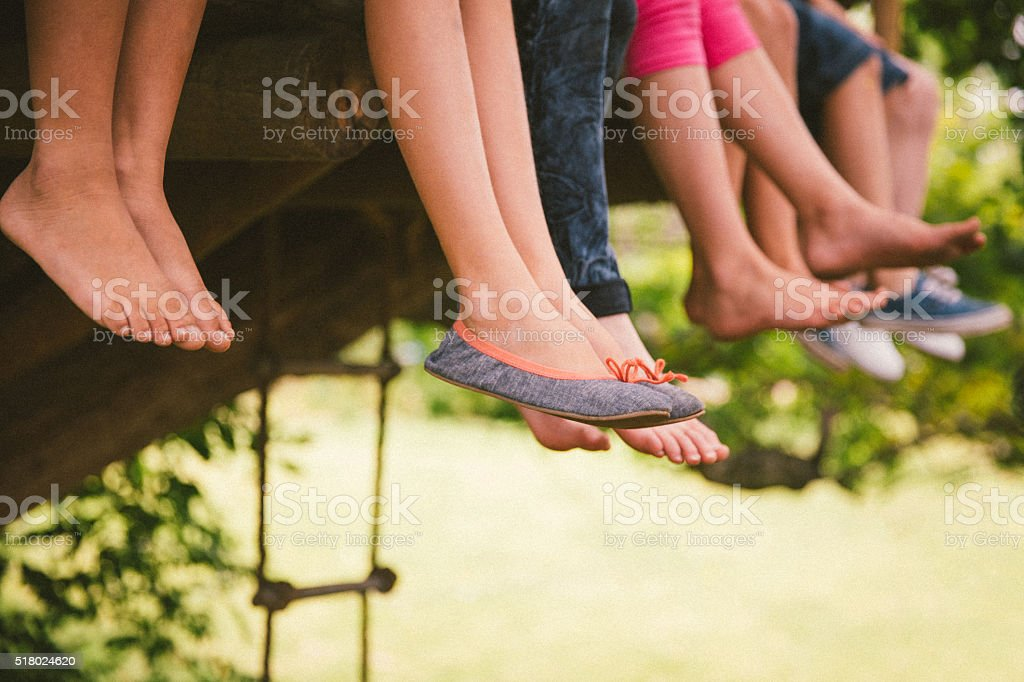 Children's feet dangling from the platform of a treehouse stock photo