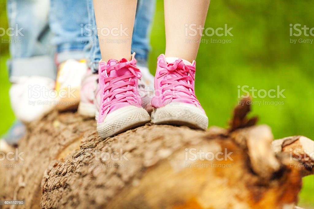 Children's feet in pink sneakers standing on a log stock photo