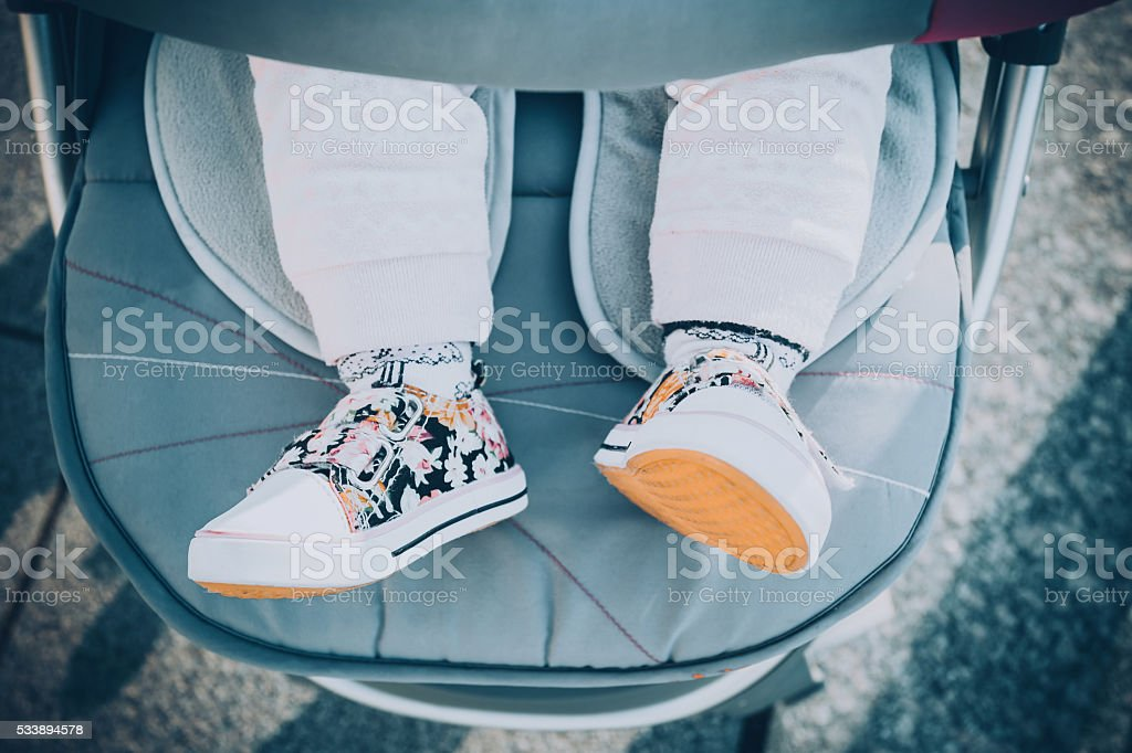 Children's feet in the baby carriage stock photo