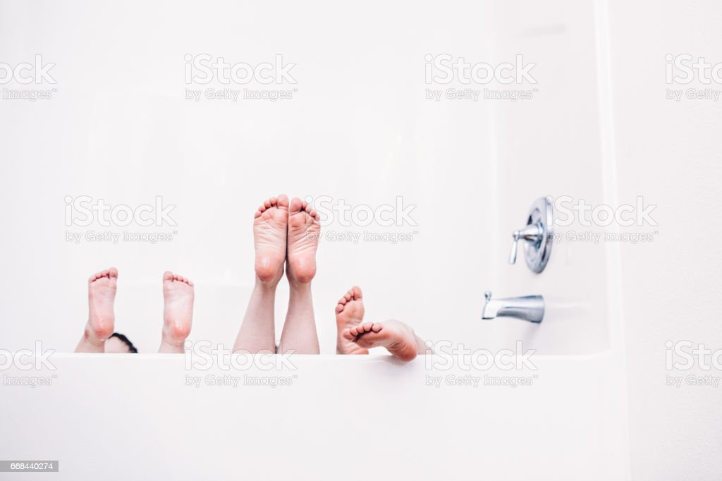 Children's Feet Stick Out of Bathtub stock photo