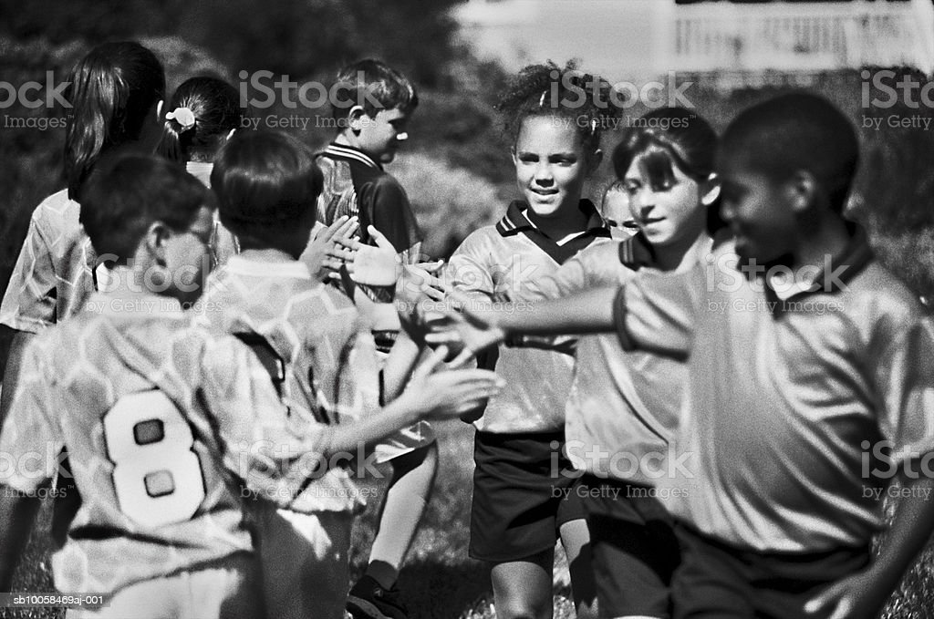 Childrens football teams shaking hands (B&W) foto de stock libre de derechos