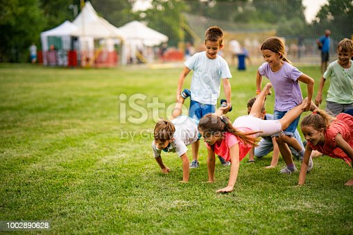 Below view of playful children having fun in wheelbarrow race