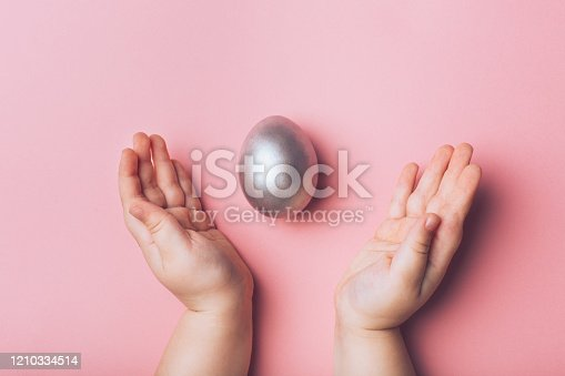 624266324 istock photo Children's hand reaches for silver Easter eggs on a pink background. 1210334514