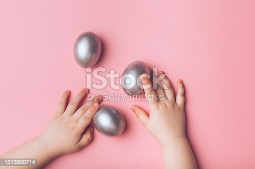 624266324 istock photo Children's hands and silver eggs on a pink background. 1213930714