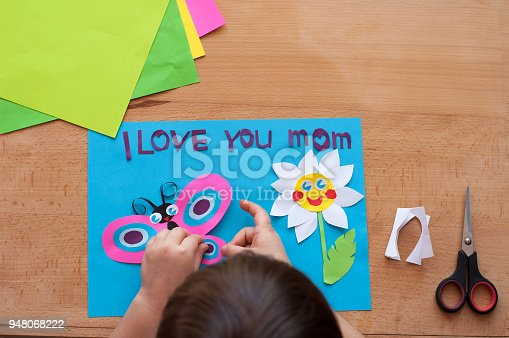 Children's hands are making greeting card for mother on the occasion of the Mother's day. Child creativity, handmade. Love to Mom. Wooden background.