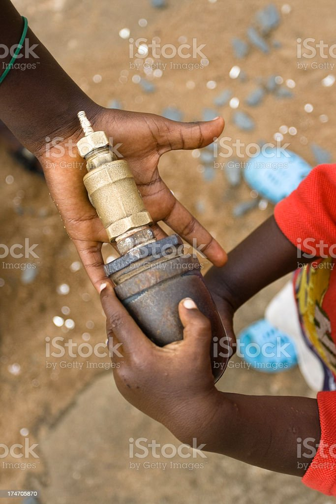 Children's Hands Around a Water Spout royalty-free stock photo