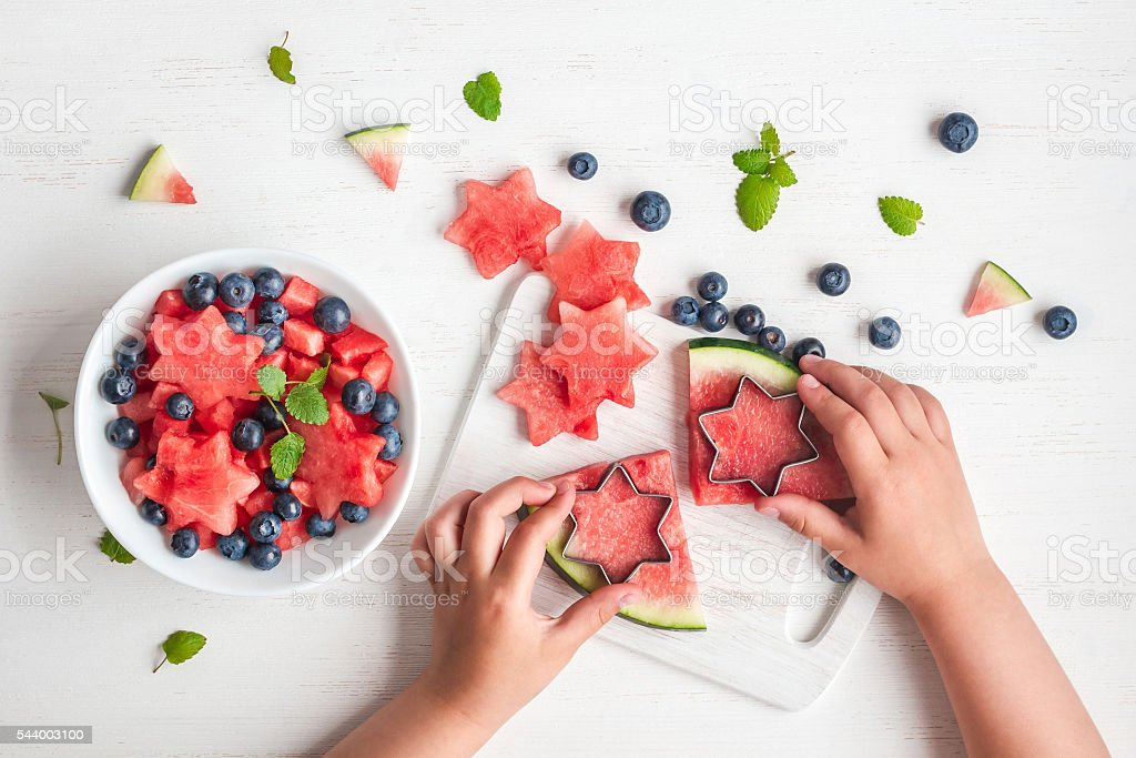 children's hands cooking salad on white table, flat lay stock photo