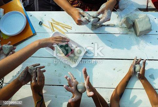 istock Children's hands crumble pieces of clay 1023998032