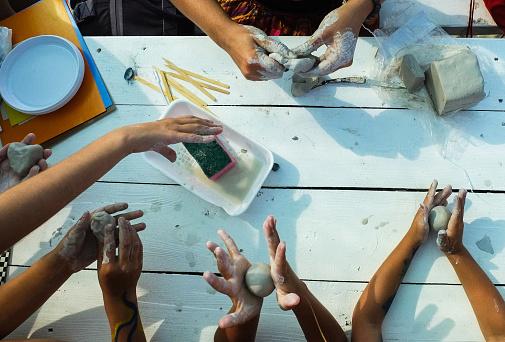 Children's hands crumble pieces of clay