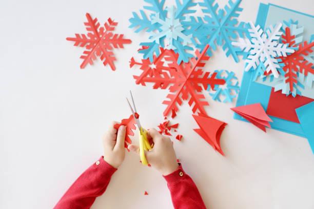 die hände von kindern auf einem weißen hintergrund blau und rot schneeflocken aus papier ausgeschnitten - winterdeko basteln stock-fotos und bilder
