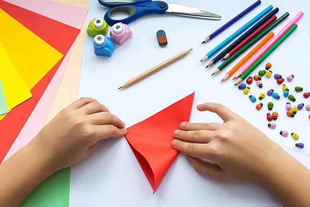children's hands do origami  bird from red paper. - origami anleitungen stock-fotos und bilder