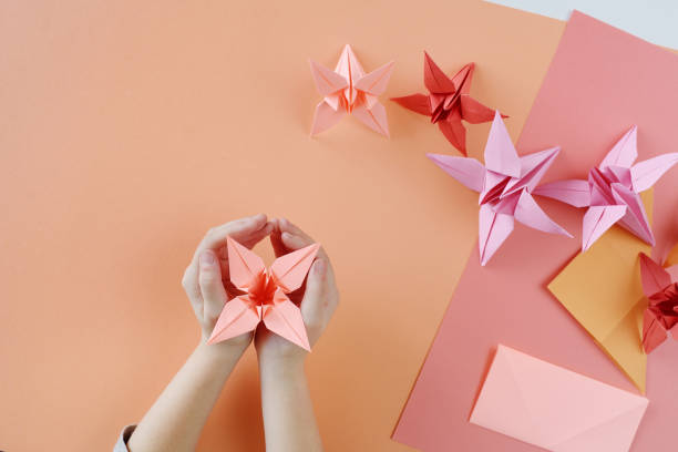 die hände der kinder machen origami aus farbigem papier auf lebendigem korallenhintergrund. - origami anleitungen stock-fotos und bilder