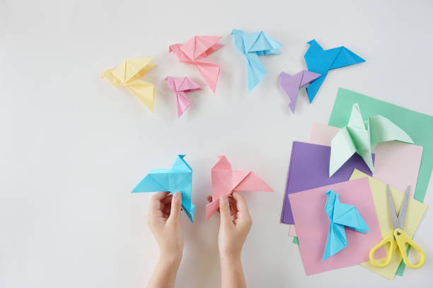 kinderhände tun origami aus farbigem papier auf weißem hintergrund. lektion von origami - origami anleitungen stock-fotos und bilder