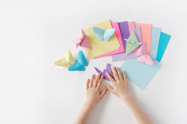 die hände von kindern tun origami aus farbigem papier auf weißem hintergrund. lektion des origami - origami anleitungen stock-fotos und bilder