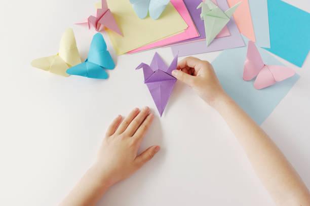 die hände von kindern tun origami aus farbigem papier auf weißem hintergrund. lektion des origami - kindergarten workshop stock-fotos und bilder