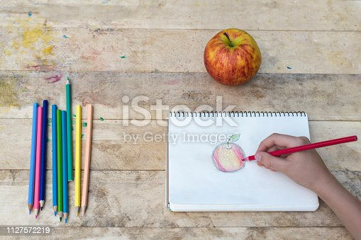 istock Children's hands draw an apple with colored pencils. Top view 1127572219