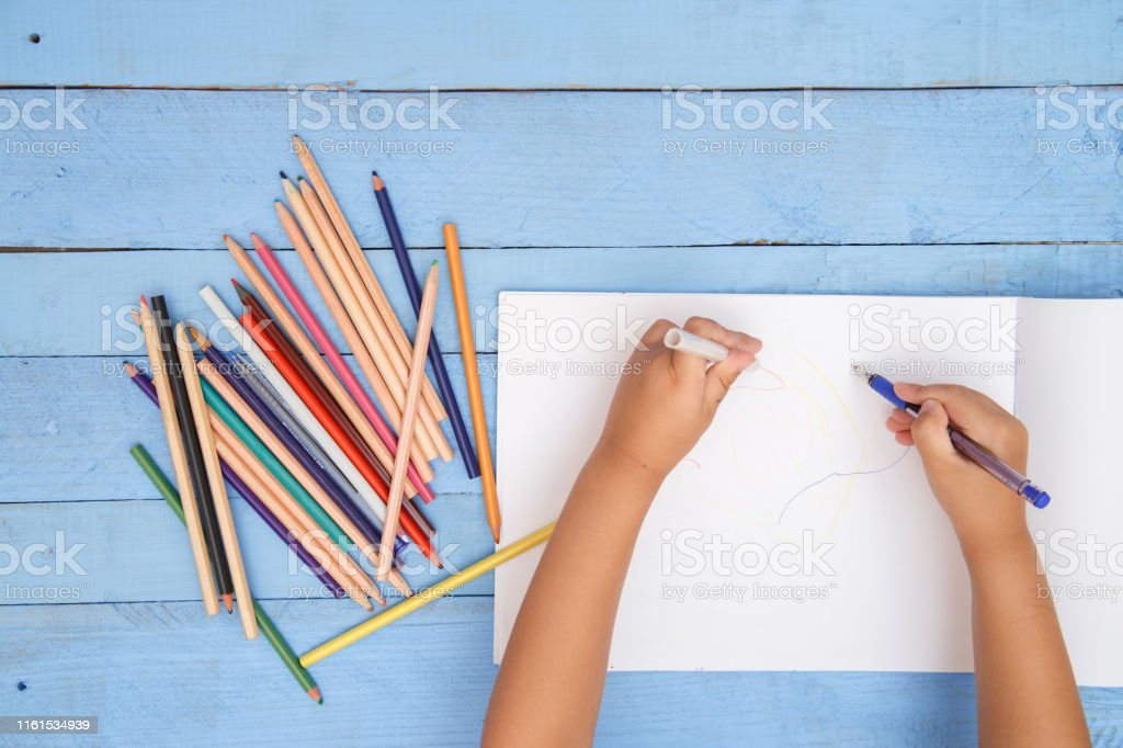 children\'s hands draw with pencils in the album on the blue table