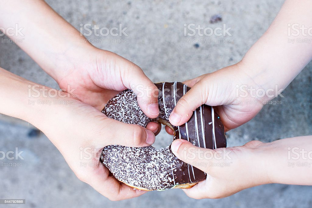 children's hands holding a chocolate donut stock photo