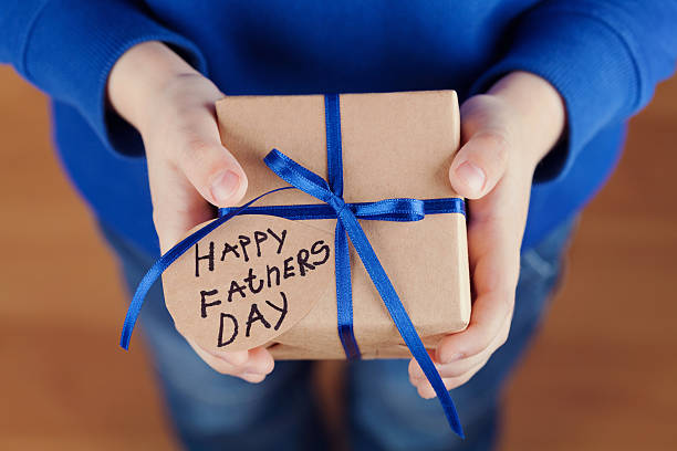 kinder hände halten geschenk, geschenk mit anhänger glücklich vatertag - vatertagsgrüße stock-fotos und bilder