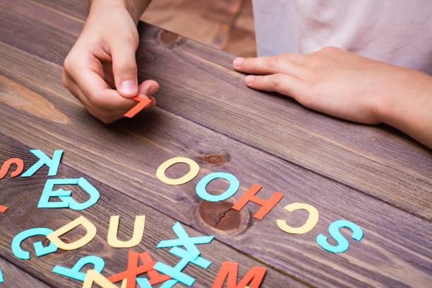 Çocukların elleri renkli oyma karton harflerden