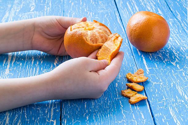 Children's hands peeling tangerine stock photo
