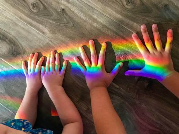 Kinderhände spielen mit einem Regenbogen – Foto