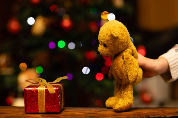 Children's hands playing with Christmas gift and teddy bear stock photo