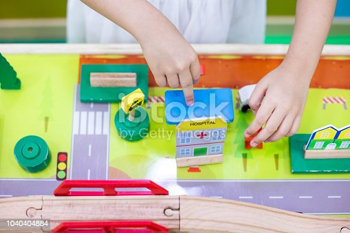 912120622 istock photo Children's hands playing wooden toy train 1040404884