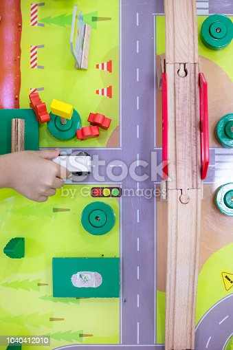 912120622 istock photo Children's hands playing wooden toy train 1040412010