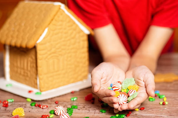 children's hands with candy to decorate the ginger house stock photo