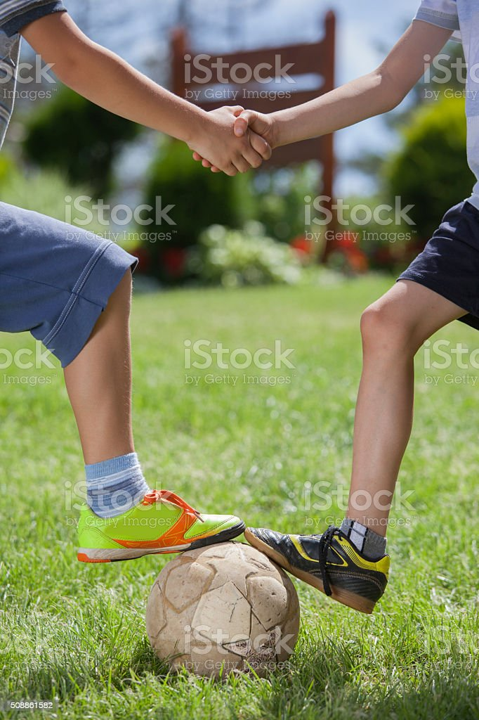 Children's handshake on soccer playground stock photo