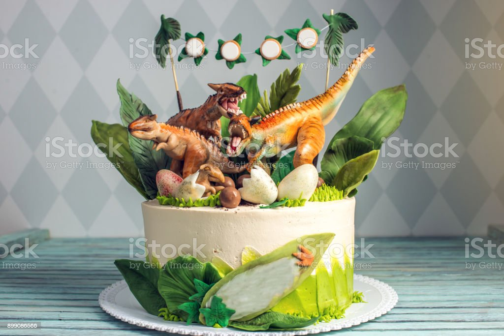 Children's holiday white cake decorated with dinosaurs in the Jurassic period jungle. Concept ideas desserts for kids stock photo