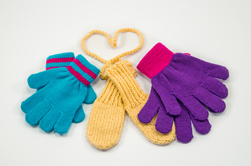 Childrens multicolored knitted mittens of manual and machine-made isolated on white background