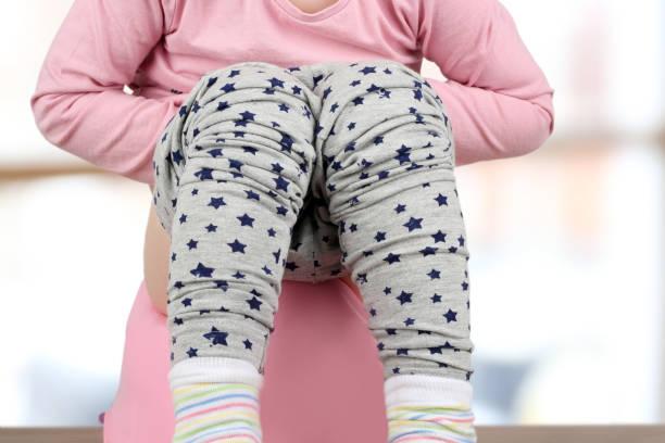 Kinderbeine hängen aus einem Kammertopf auf blauem Grund – Foto