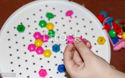 istock children's mosaic. the child lays a flower out of a colored plastic mosaic. the child's hand holds a bright plastic mosaic piece. training, development of children's motor skills. 922556270